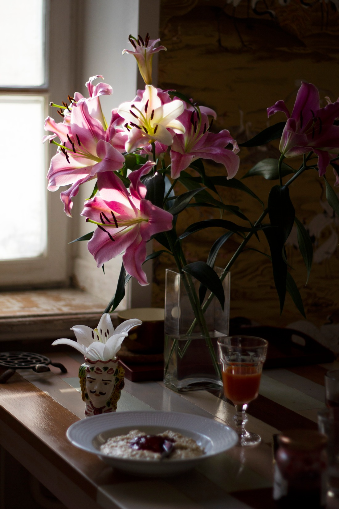 pink and white lilies and a sicilian ceramic head vase during breakfast hour